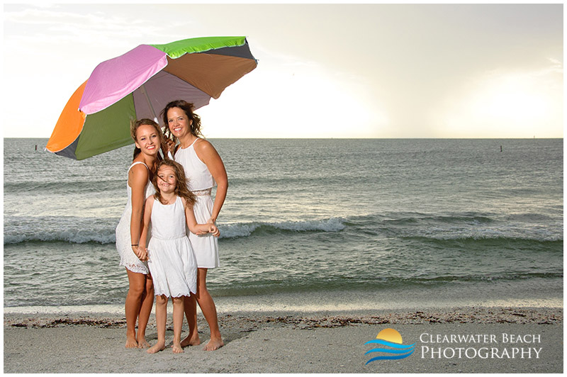 Family holding umbrella on Clearwater Beach